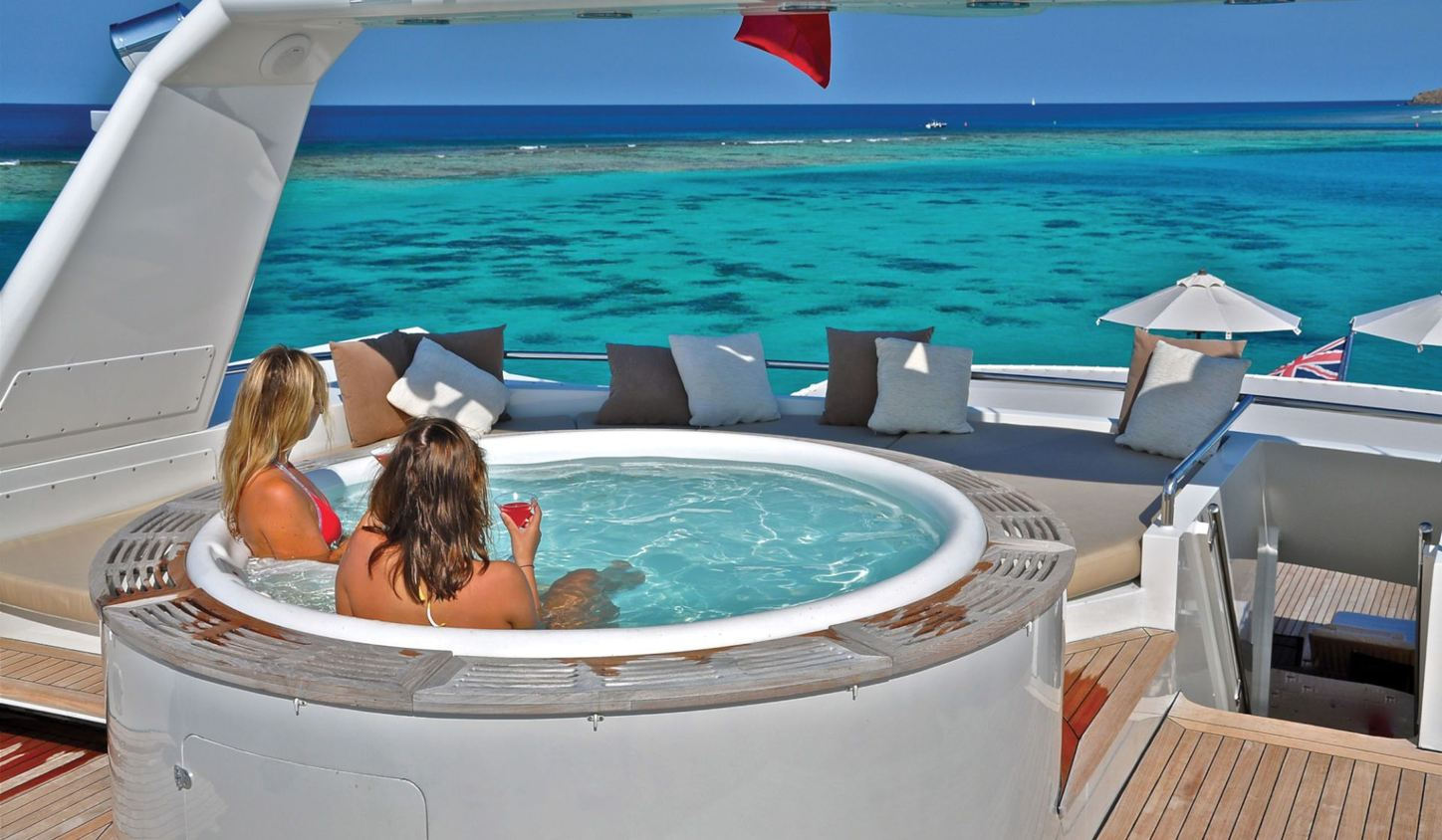 charter guests relax in the spa pool on the sundeck of superyacht LIONSHARE