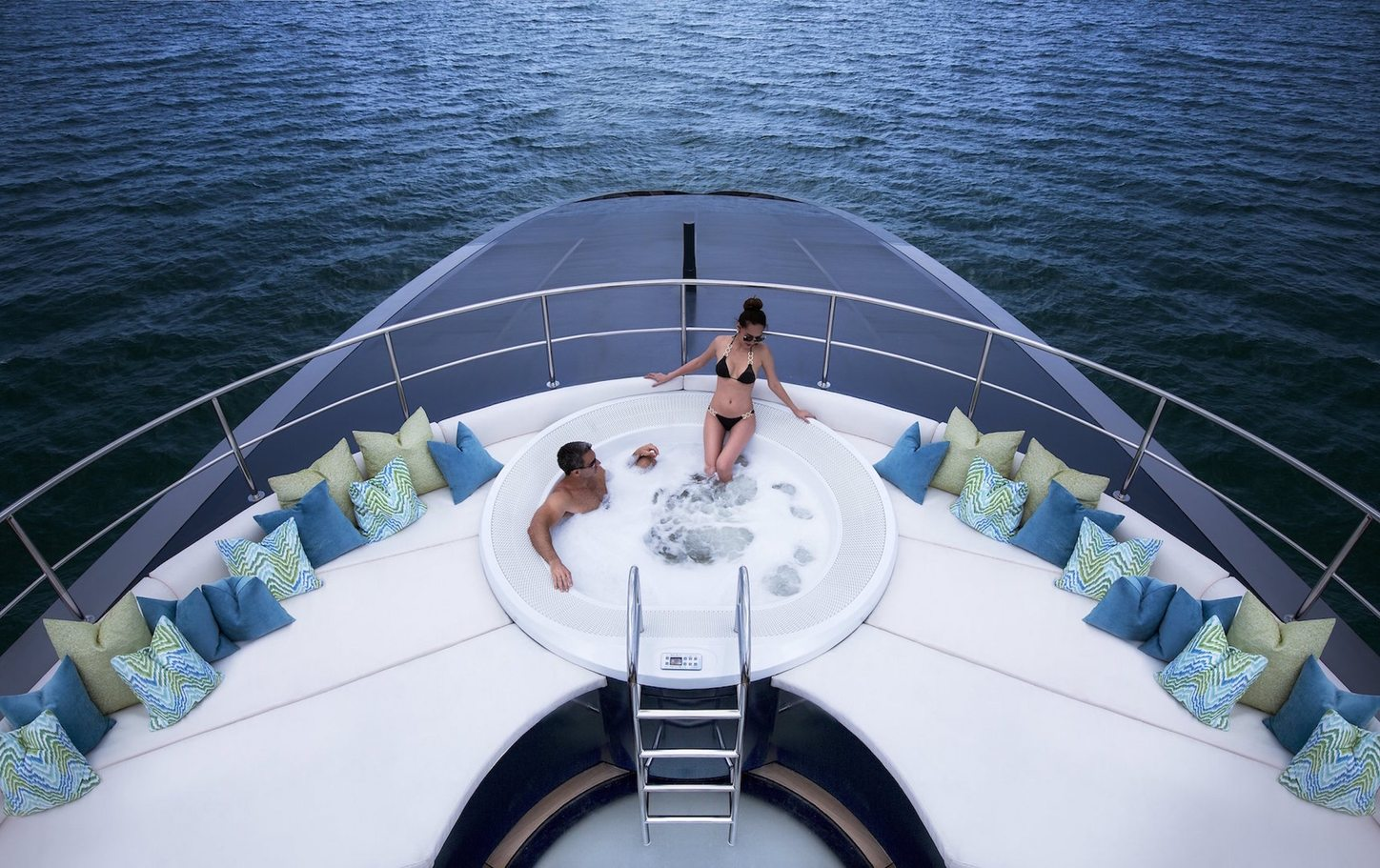 charter guests relax in the spa pool on the sundeck of superyacht Ocean Emerald