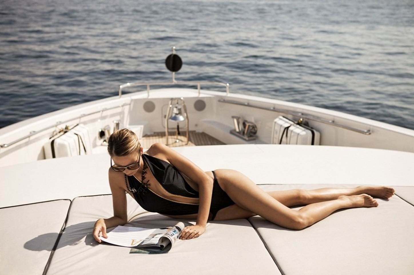 female charter guest lounges on sunpads while reading a magazine on the foredeck of superyacht AURELIA