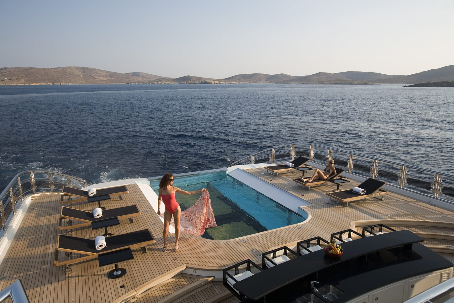 superyacht ALFA NERO infinity pool with women reclining nearby