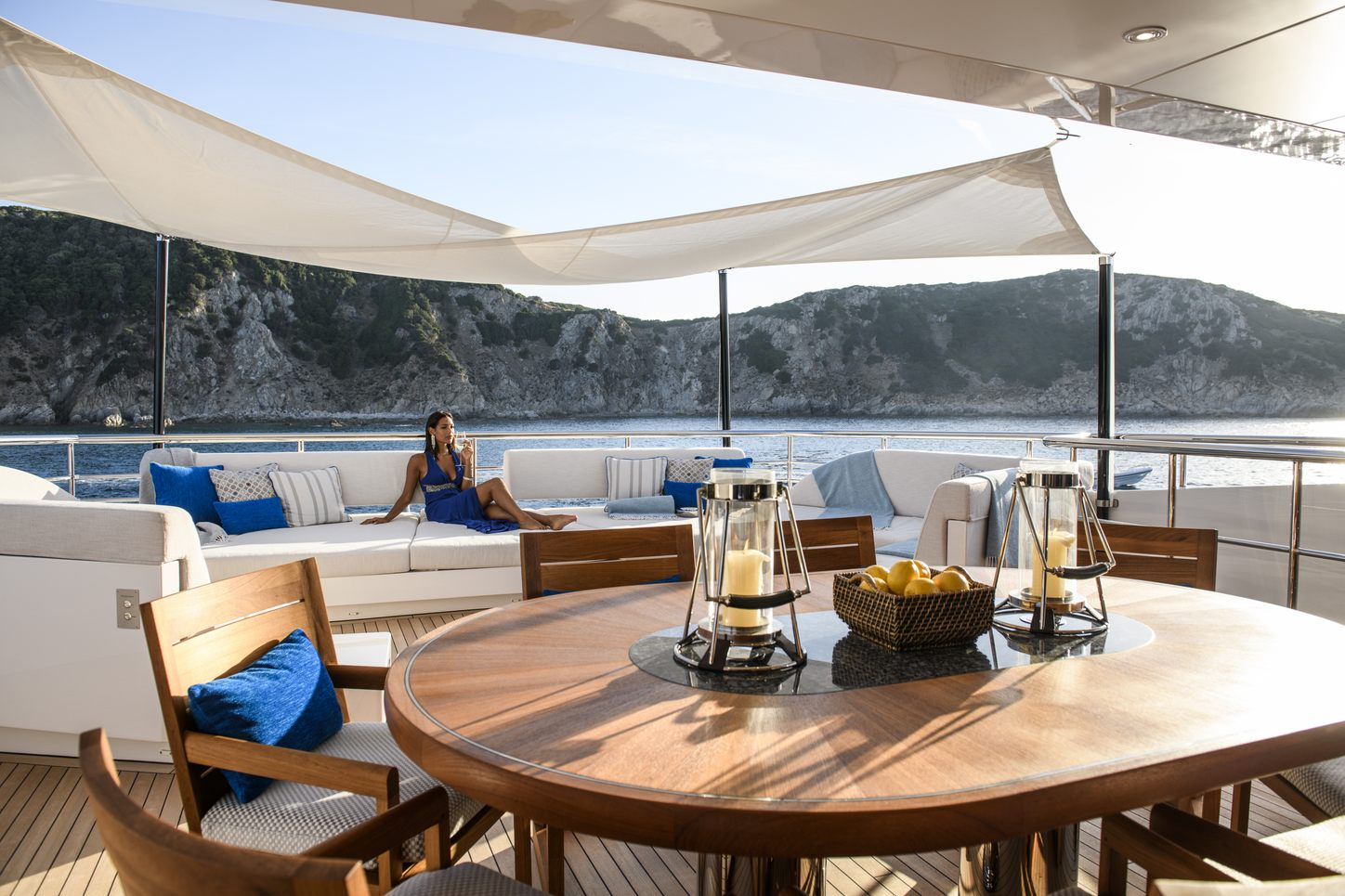 Charter guest enjoys aft deck of luxury yacht IRISHA, with bowl of lemons on table