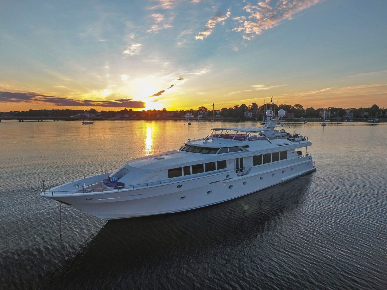 motor yacht SAVANNAH anchors on a yacht charter with the sun setting over the horizon