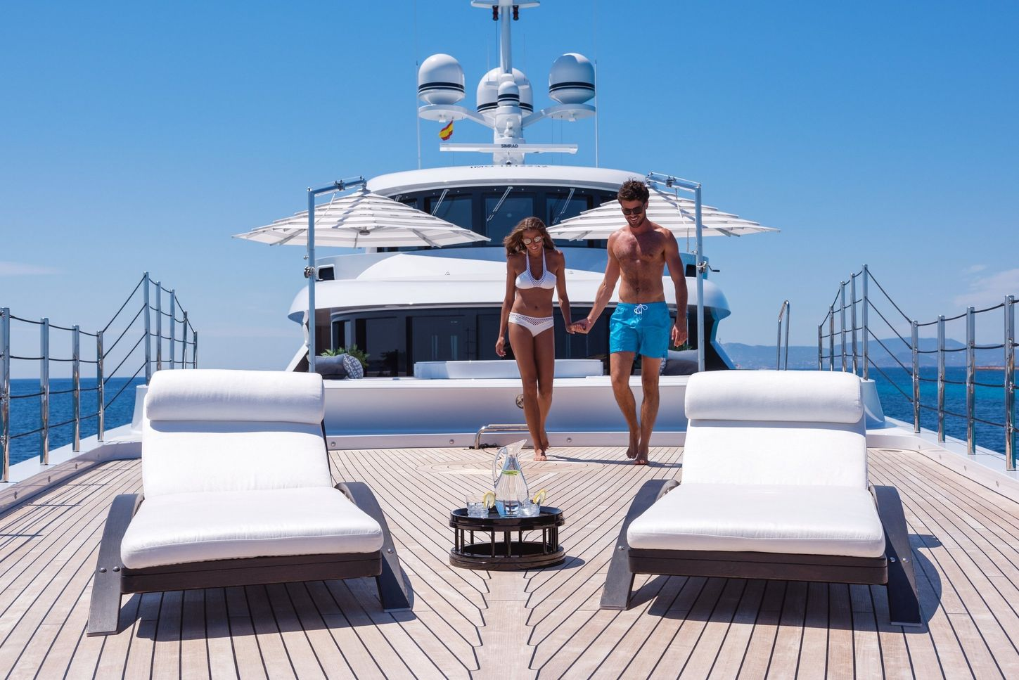 A man and woman in swimwear holding hands as they walk towards sunloungers on board a superyacht