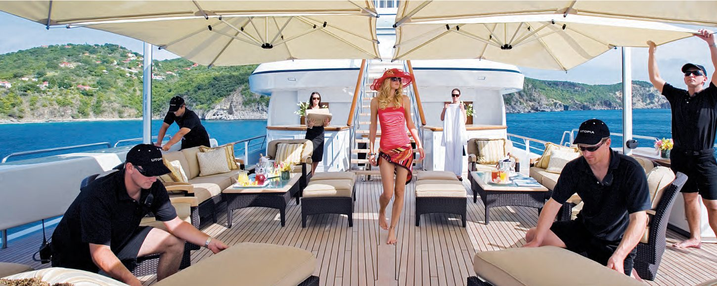 Charter guest on sundeck of luxury yacht UTOPIA surrounded by crew