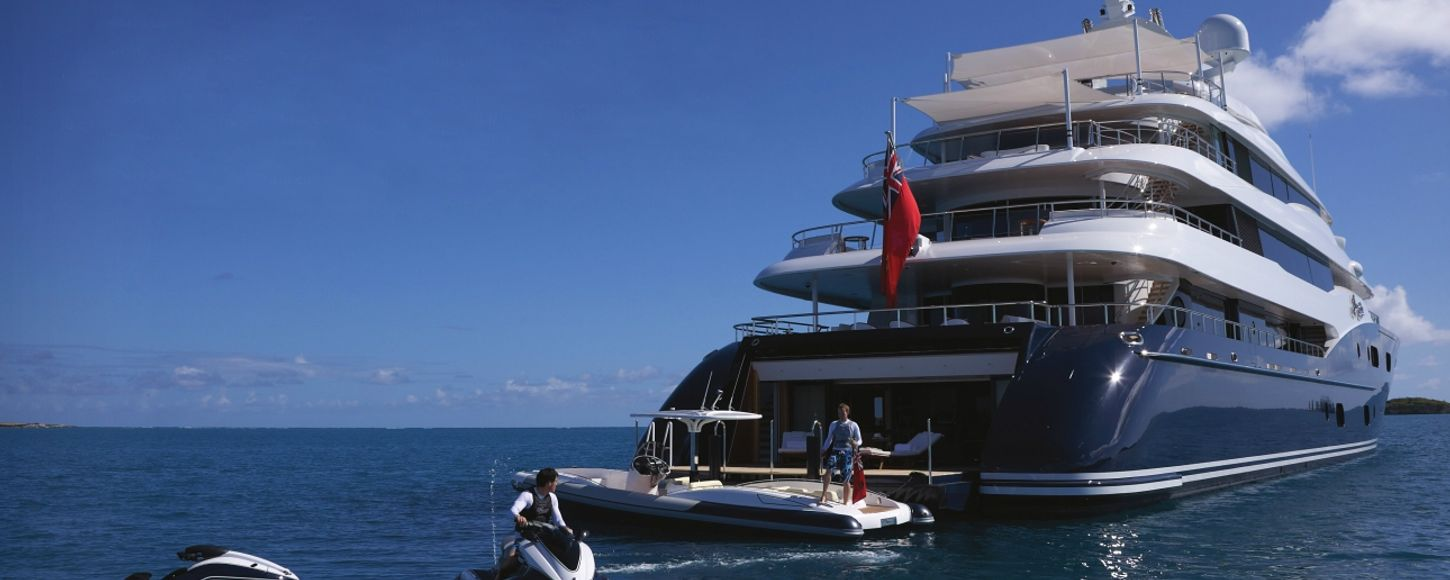 Motor yacht Amaryllis aft view with charter guests playing on jet ski and tender