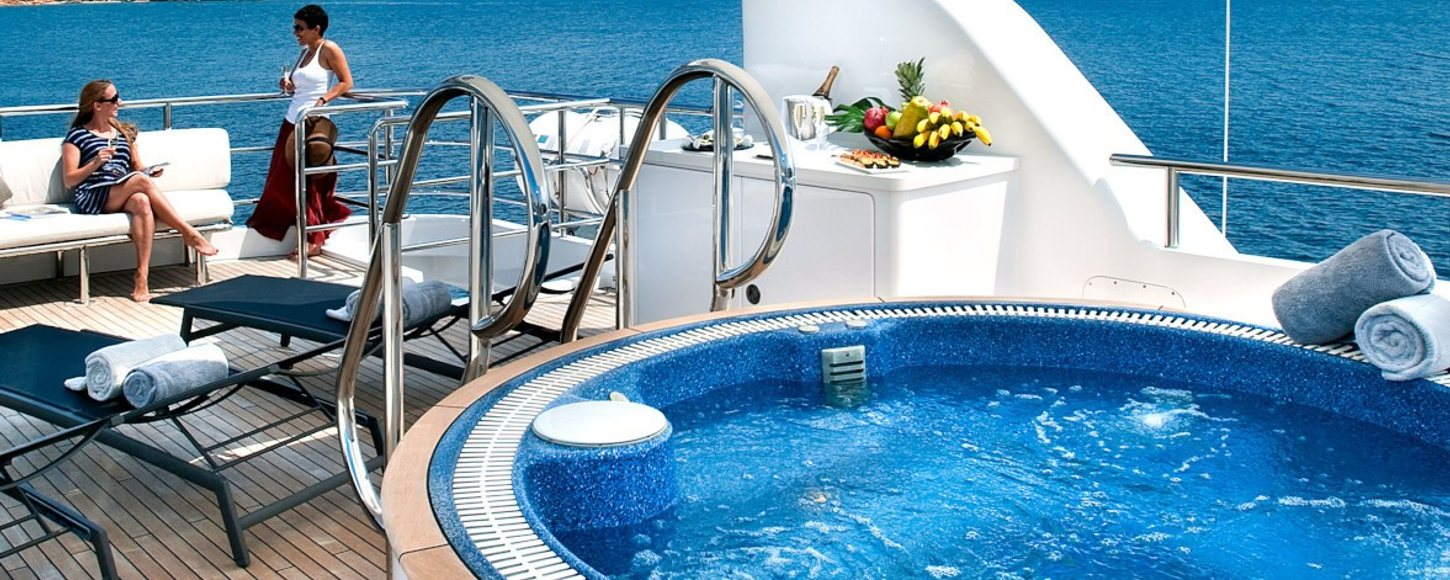 Charter guests on board superyacht relaxing in the sun, with jacuzzi pool in foreground