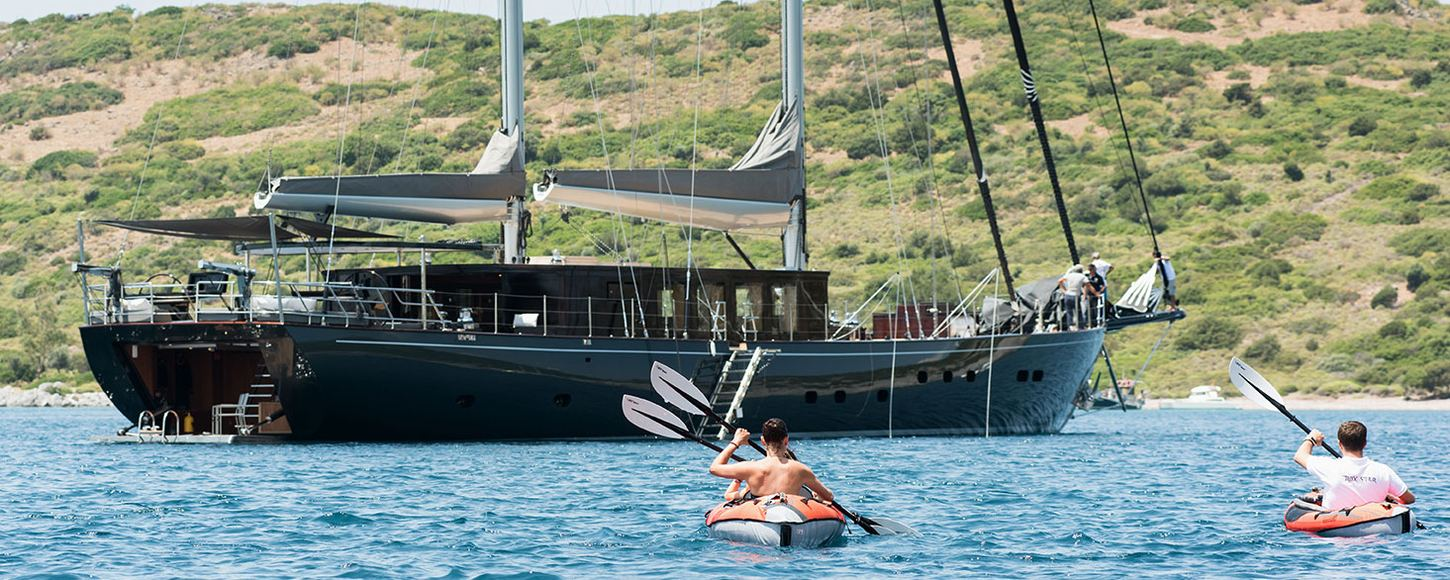 sailing yacht Rox Star anchored on charter with guests enjoying kayaks