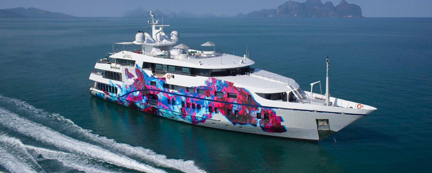 A white superyacht with a colorfully decorated hull