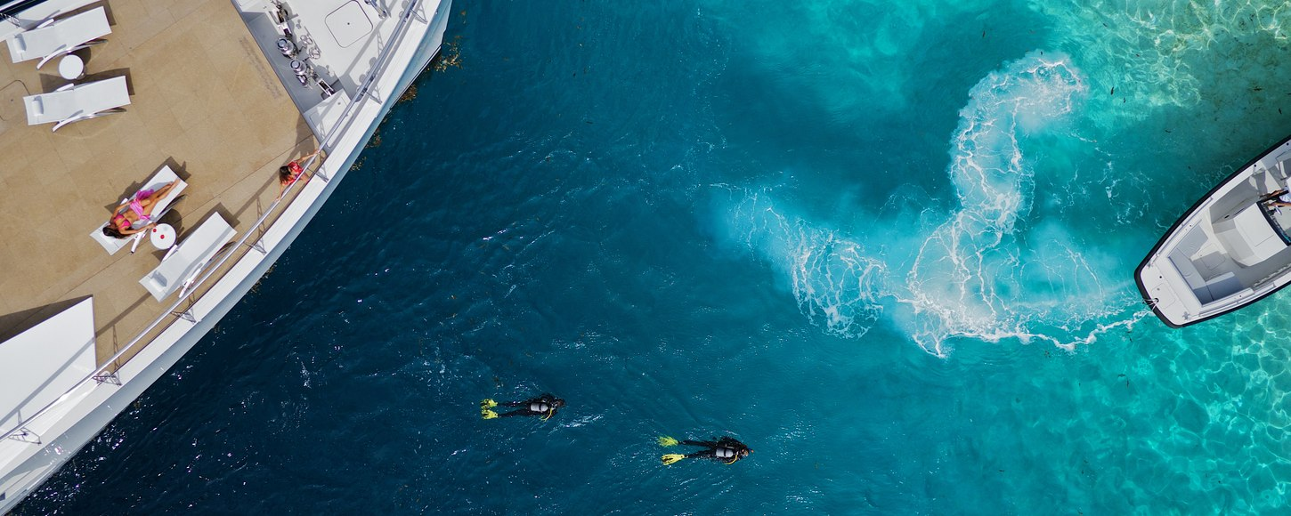 Aerial view of BIG FISH expedition yacht with charter guests on deck