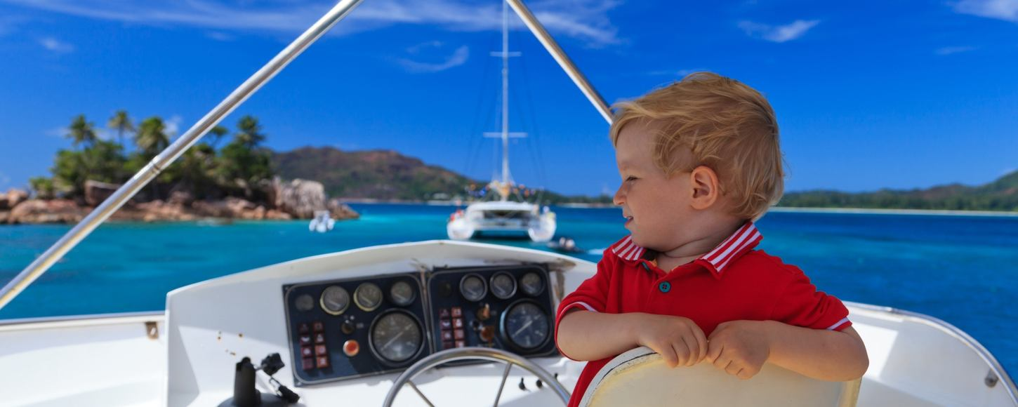 Young child sitting at the wheel of a charter yacht