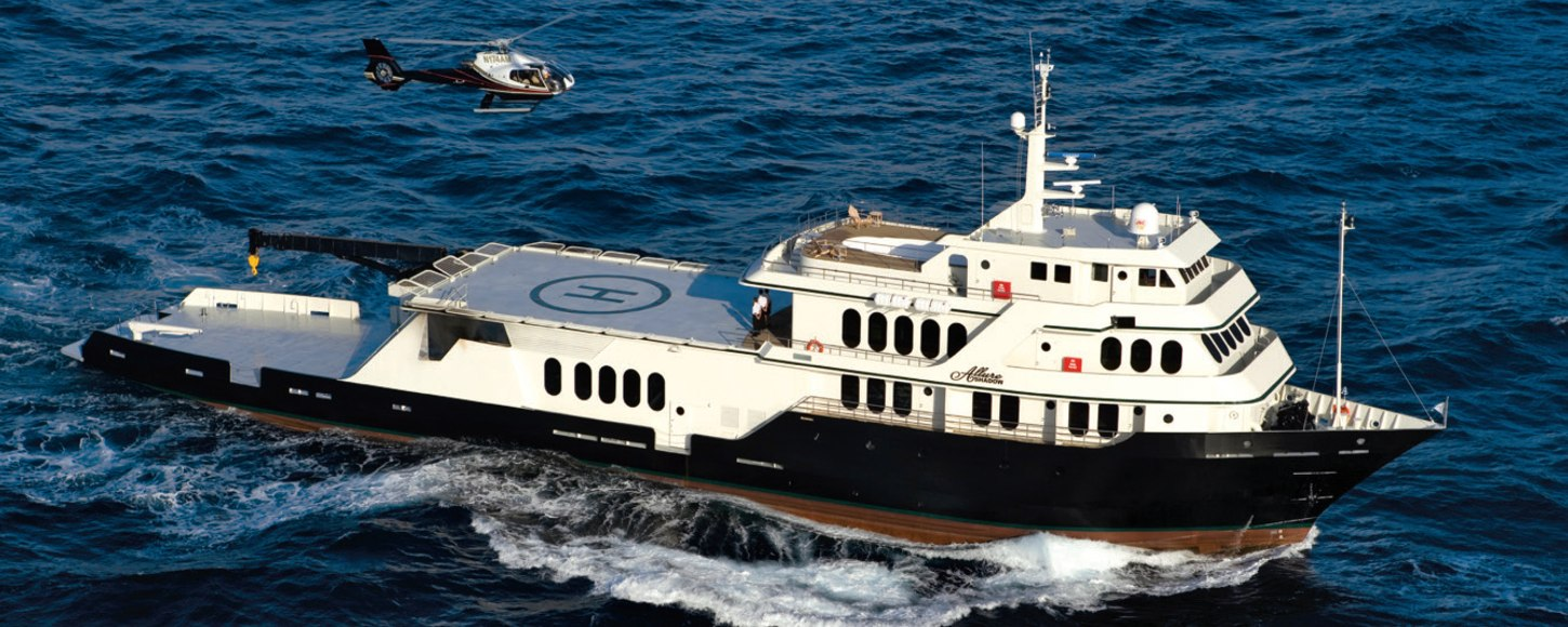 expedition yacht GLOBAL underway with helicopter in tow