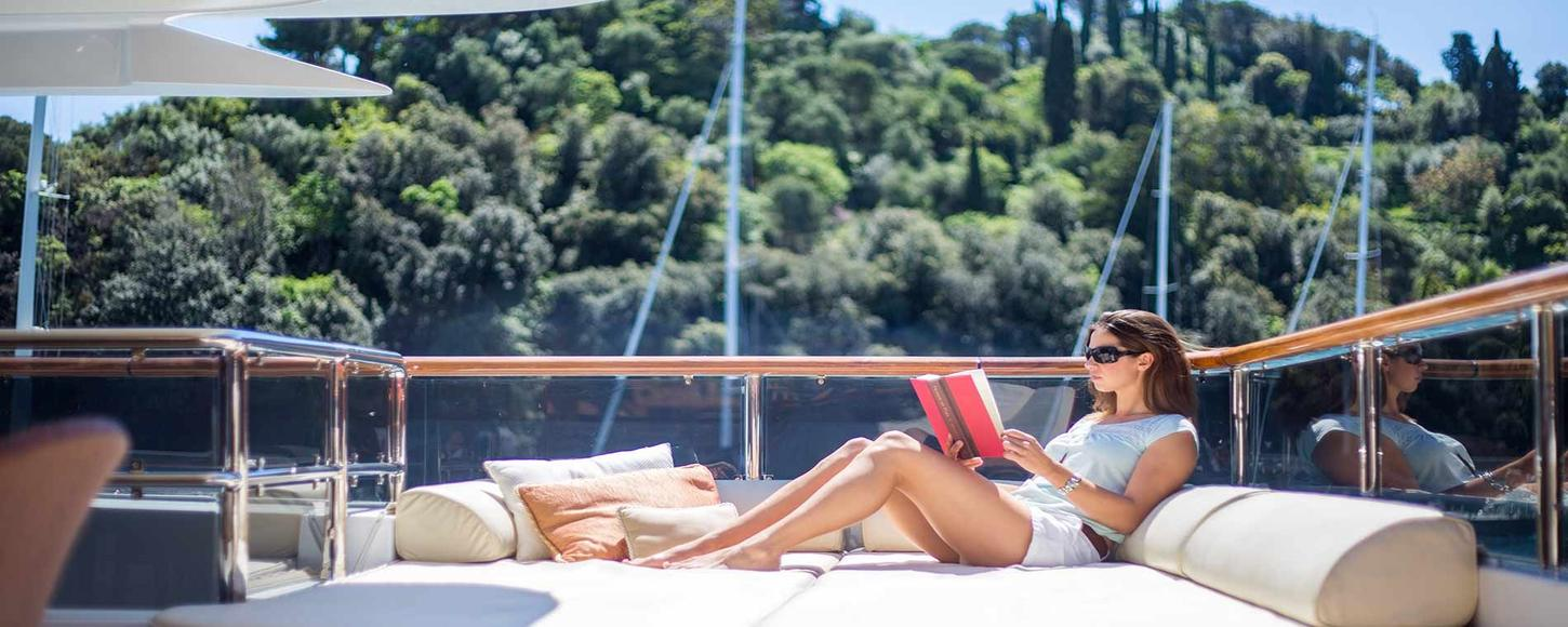 Charter guest relaxes on board luxury superyacht DIANE
