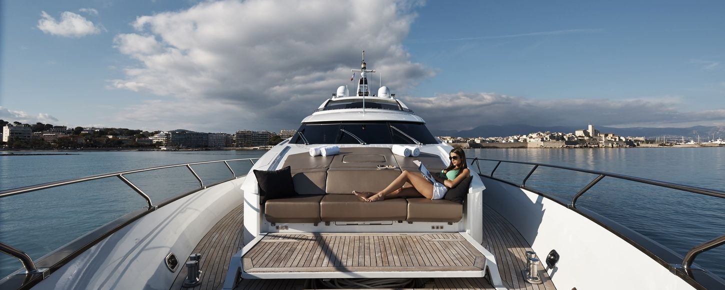 Charter guest reading magazine on foredeck seating on superyacht Quantum