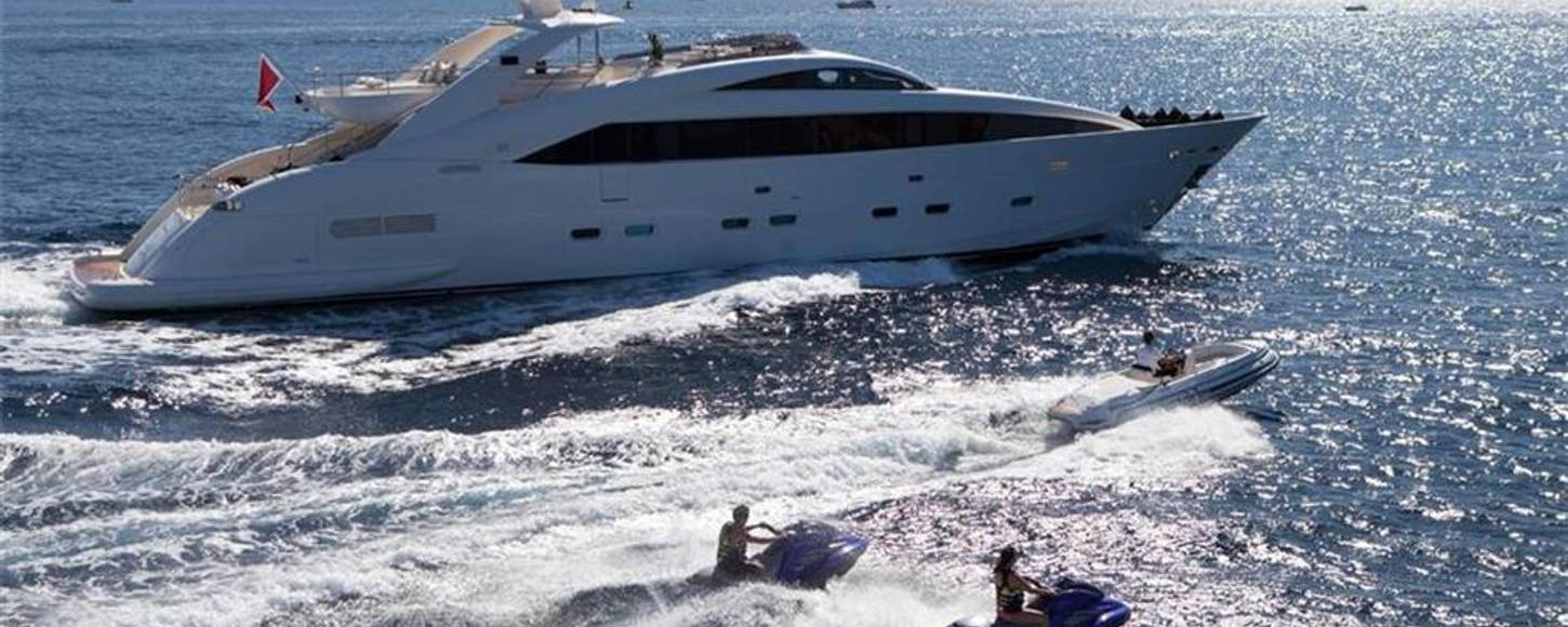 Motor yacht Whispering Angel cruising with jet skis on a yacht charter