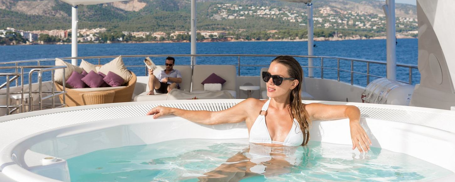 female charter guest relaxes in Jacuzzi on board sundeck of motor yacht GO