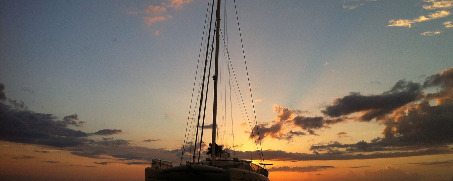 Catamaran Orion sailing on charter in Caribbean with a beautiful sunset