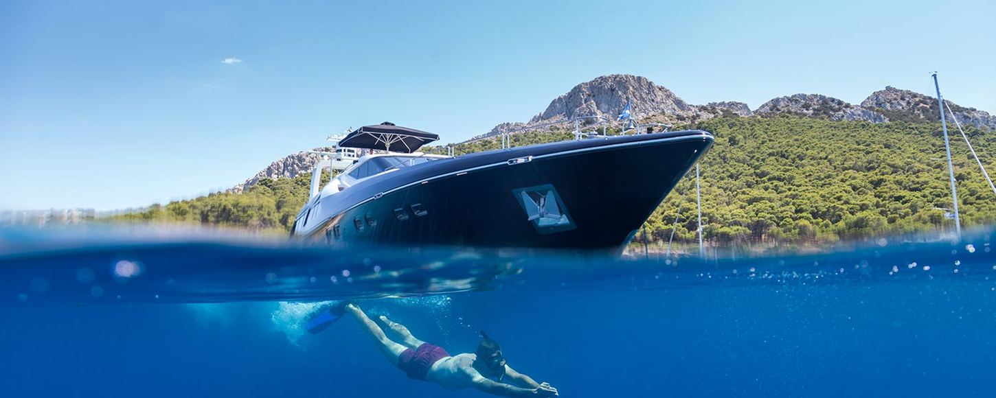 Charter guest swims in the waters of the Mediterranean in Greece alongside motor yacht AQUARELLA