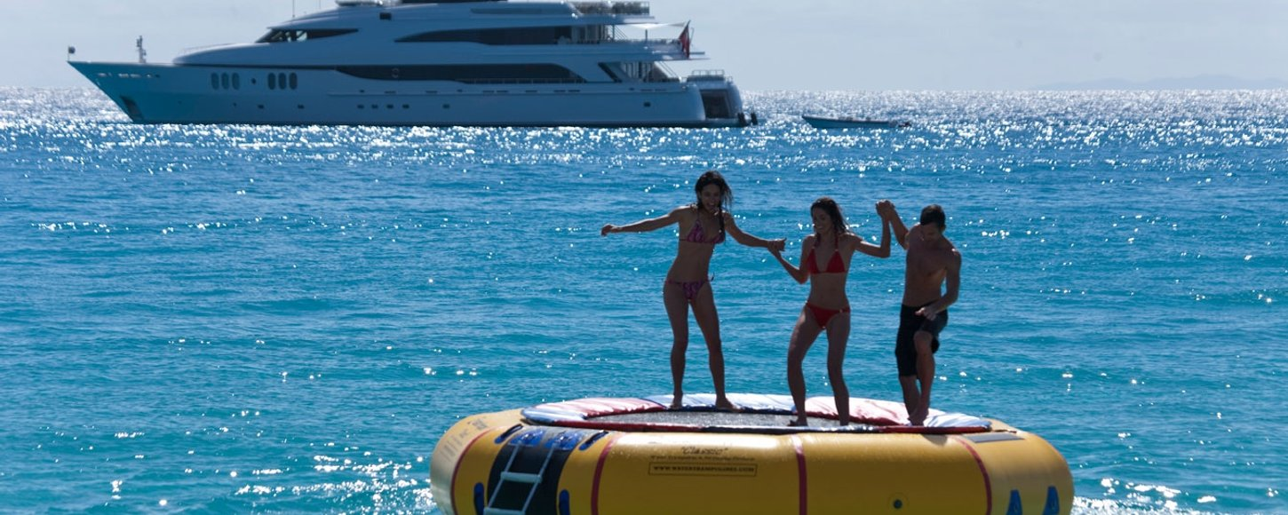 Charter guests balancing ontop of a large inflatable trampoline with charter yacht 'Diamond A' in the background