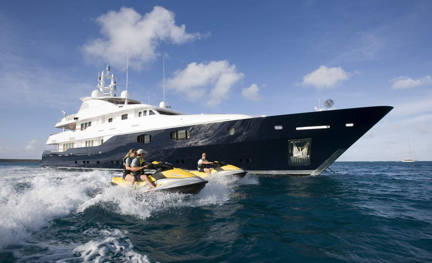 motor yacht ODESSA cruises through the water alongside jet skis on a Caribbean yacht charter