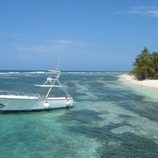 View of a typical Caribbean beach, with fishing boat moored in shallow water.