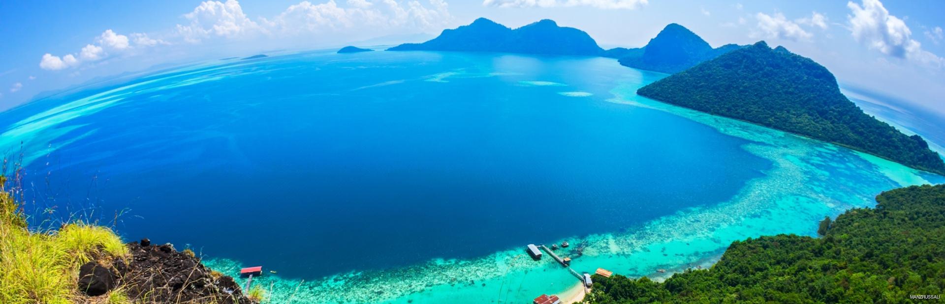 Green Malaysian coastline with hills and beautiful blue sea