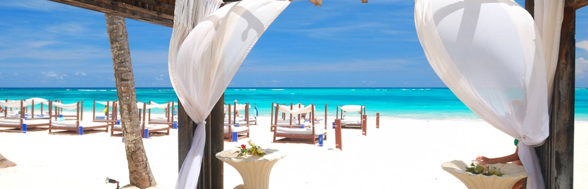 Wooden gazebo with white waving curtains on the beach