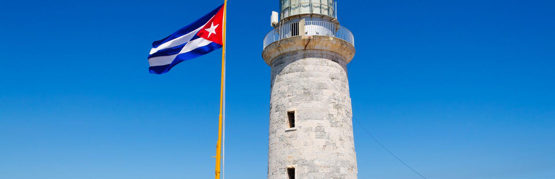 Waving Cuba flag next to the el Morro lighthouse