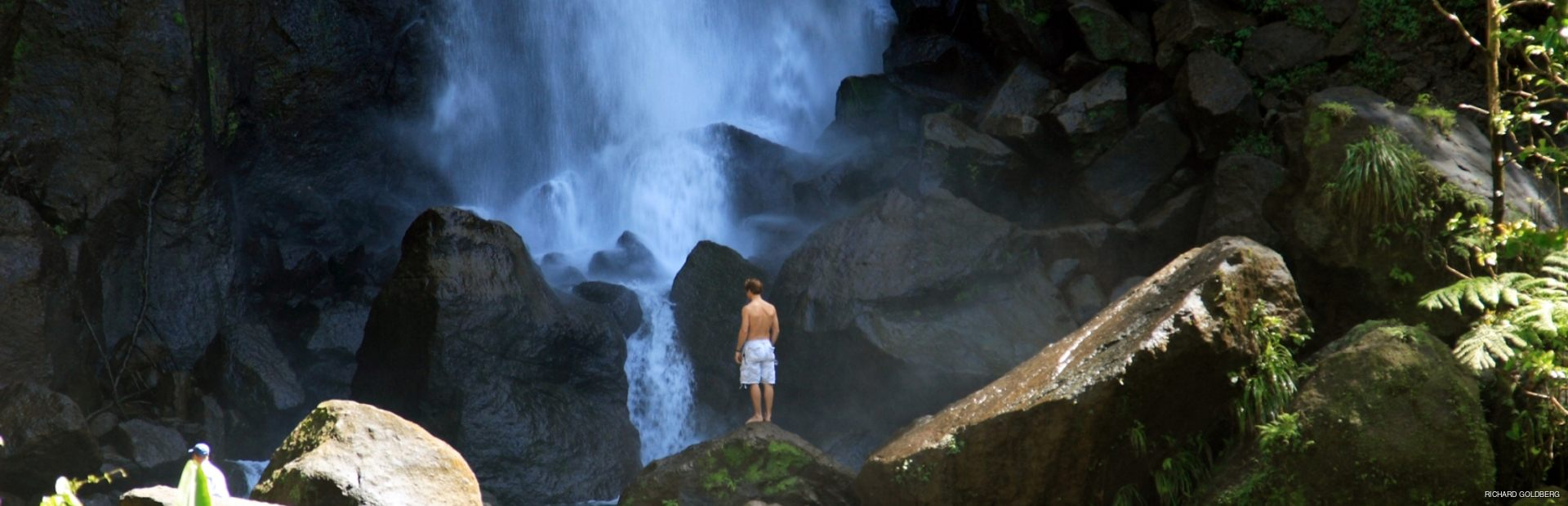 Man standing on the rock and observing azure waterfall