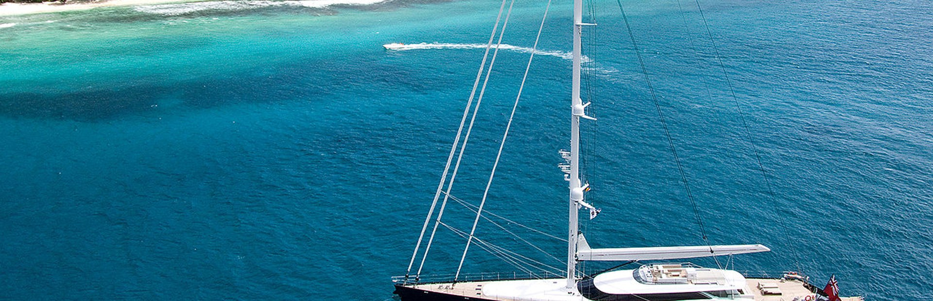 An Allloy Yachts charter superyacht at anchore off tropical island
