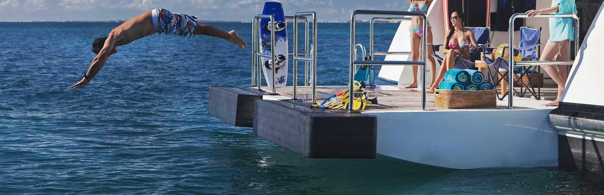 Charter guest diving off swim platform of Jaguar Superyacht
