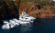 luxury yacht jacozami in little bay in the mediterranean, with two charter guests on jet skis riding alongside