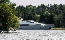 Superyacht Queen of Sheba on water with forest in the background