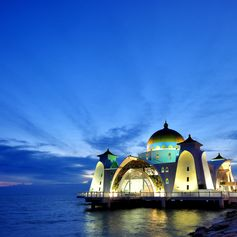 Beautiful lighted mosque on the sea at sunset