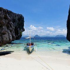 Boat at beach between two dark cliffs