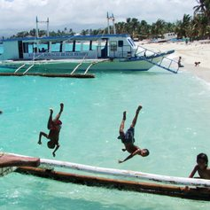 Children jumping from the boat to the sea