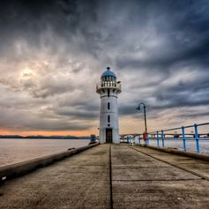 White lighthouse at the on of the jetty