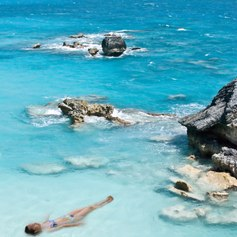 Woman relaxing in beautiful, blue crystal clean saewater