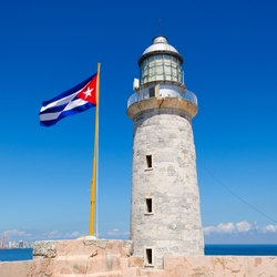 Waving Cuba flag next to the el Morro lighthouse