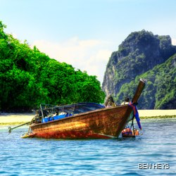 Boat on the sea in front of the tropical Asian forest