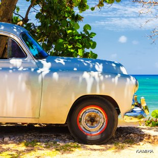 A white classic car on Cuba's coastline