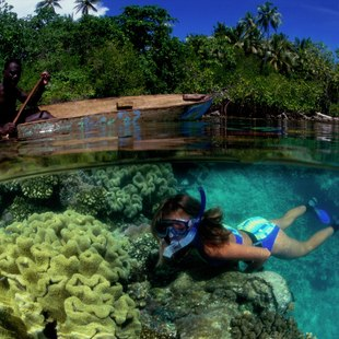 Snorkelling woman and kayaking native