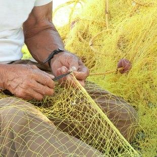 Fisherman mending his net in Poros, Greece
