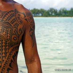 A man with a traditional Polynesian tattoos on his arm and chest