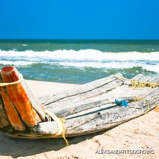 Primitive boat on the Indian beach made of wood tied with string