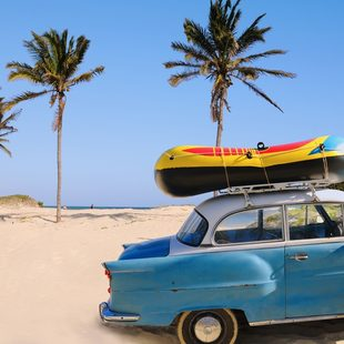 Old blue car with surfboard on the top parked on the beach with palm trees