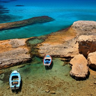 Fishing Boats off the Rocky Shores of Milos Island