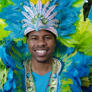 Smiling man in a green and blue carnival costume