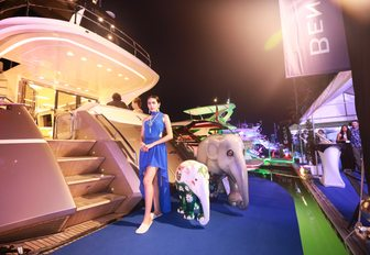 a women greets guests arriving to a yacht at night at the Thailand Yacht Show & Rendezvous