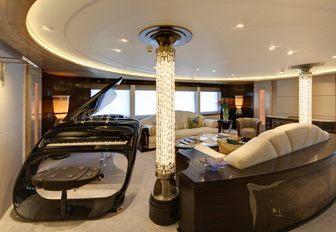 A sleek black grand piano in the main salon of superyacht AMARYLLIS