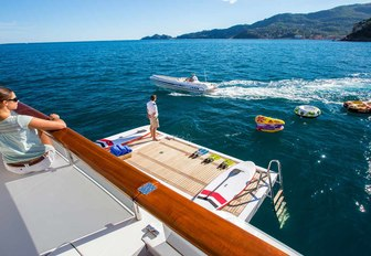guest aboard motor yacht DIANE looks on at fold-down swim platform and water toys in the sea